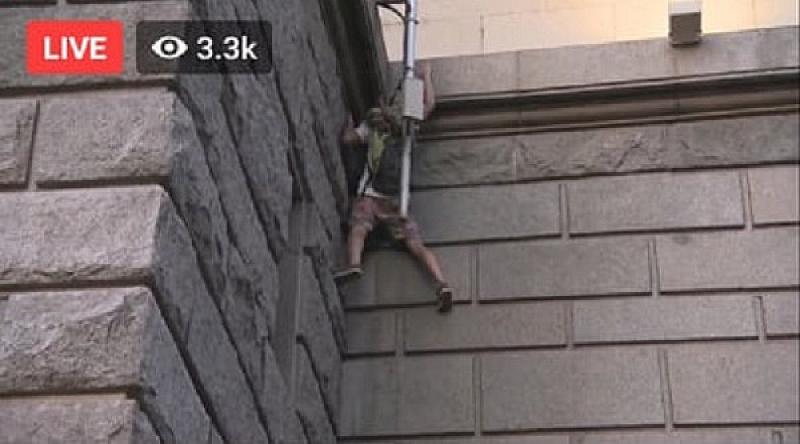 Младеж от протестиращите се покатери по стената на сградата на